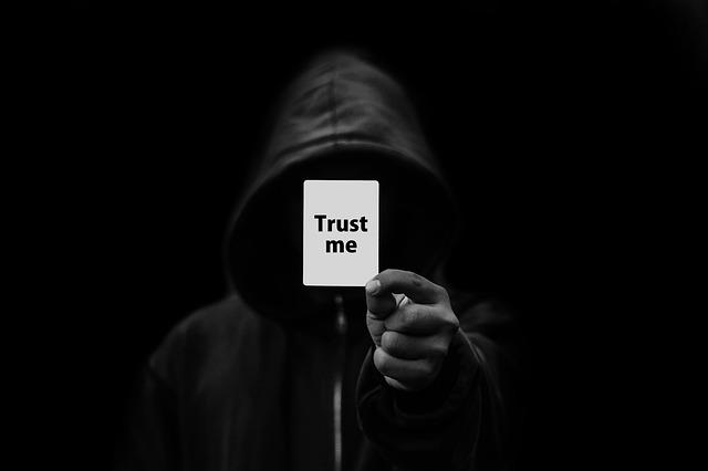 člověk v kapuci ukazující ze tmy kartičku s nápisem trust me